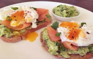 Avocado on toasted rye bread with salmon and poached egg