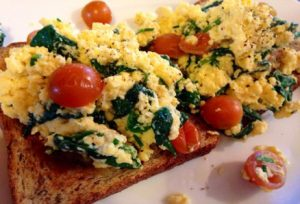 Scrambled eggs with toasted rye, spinach and tomatoes